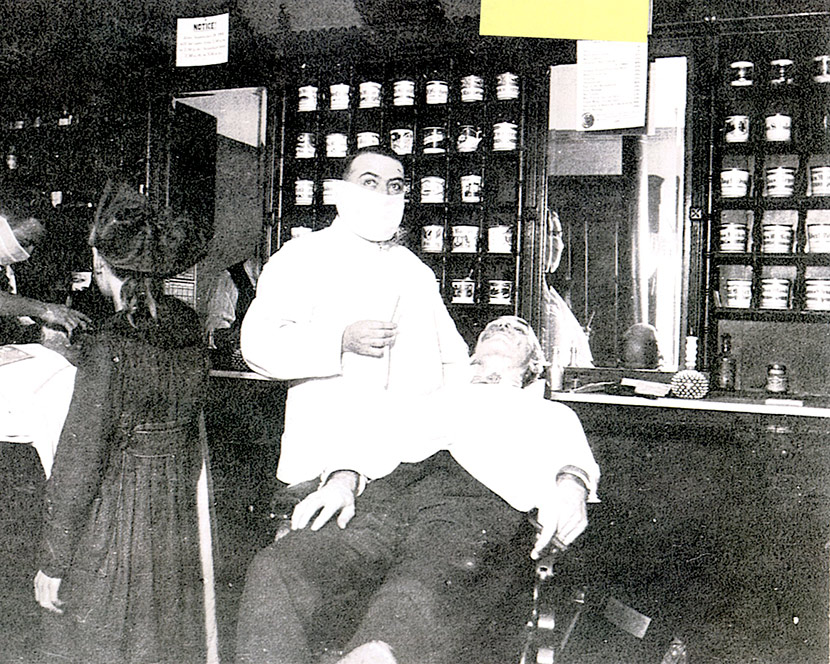 A Cincinnati barber wears a mask while giving a customer a shave.