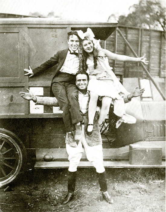 Douglas Fairbanks holding Charlie Chaplin and Mary Pickford on his shoulders in Hollywood. During the epidemic, each star had two films in release. In many cities, moviegoers had to wait until closure orders were lifted in order to see Fairbanks, Chaplin, and Pickford on the silver screen.