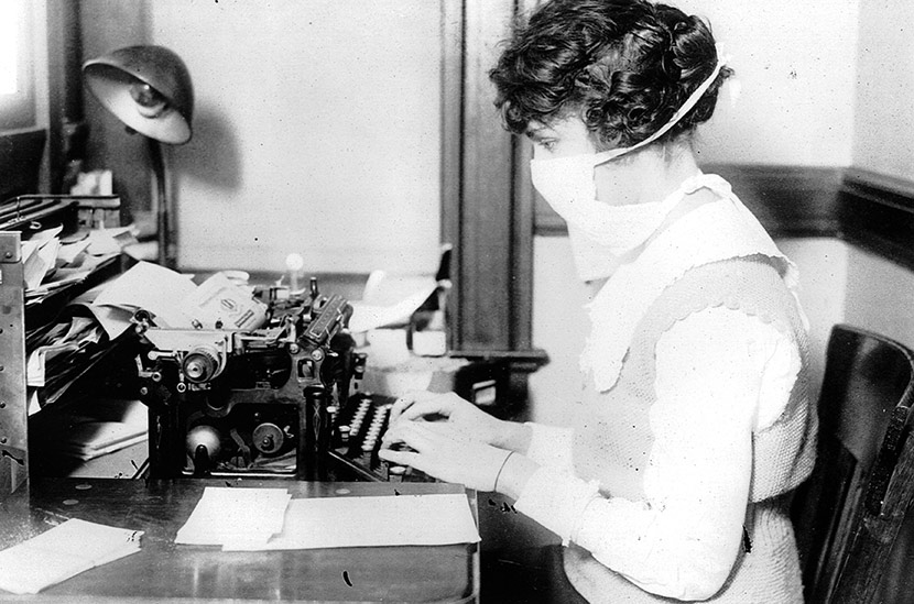 A New York City typist wears a flu mask while at her desk, October 16, 1918.