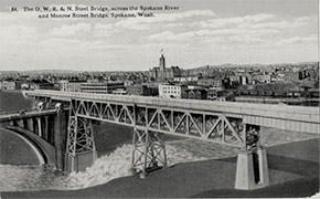 A view of the Oregon-Washington Railroad and Navigation Company bridge and the Monroe Street Bridge crossing the Spokane River, with the city in the background.