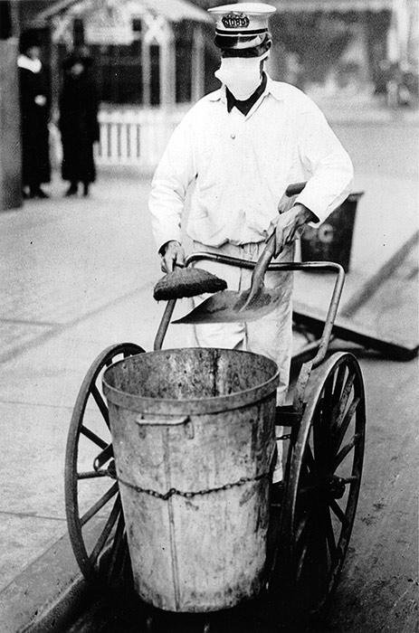 A New York City street sweeper goes about his business while wearing a gauze mask to guard against influenza, October 16, 1918.