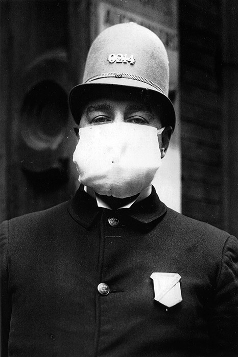 A New York City police officer wears a flu mask while on duty, October 7, 1918.