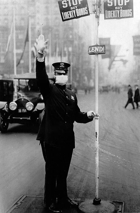 A New York City traffic cop directs vehicles while wearing a flu mask, October 16, 1918.