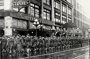 The 39th Regiment marches down 2nd Ave. with their flu masks on, passing Cheasty's Haberdashery, ca. October/November 1918.